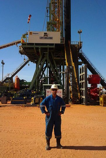 man in protective gear standing in front of large drilling machinery